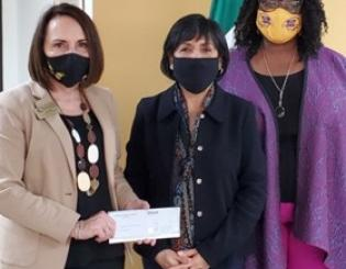 three people stand together wearing face masks