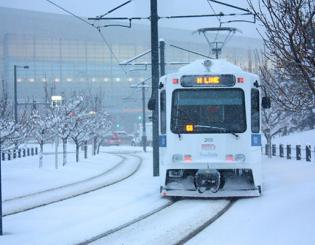 light rail train on tracks in snow