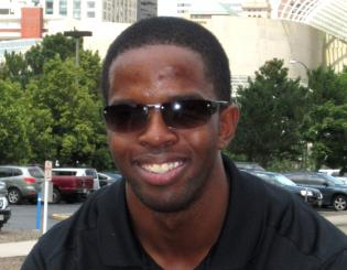 young man with sunglasses smiles at the camera