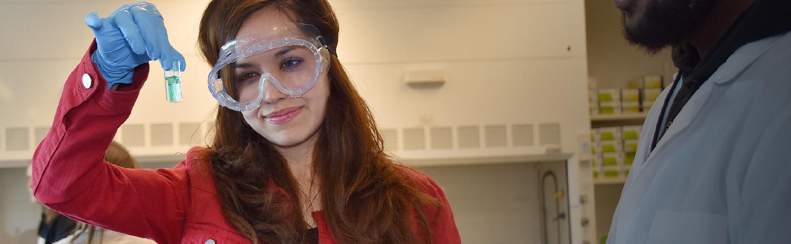 female student in protective eye wear in science lab