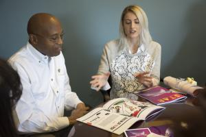black man in a white shirt, seated talking to a blond woman and looking at a magazine