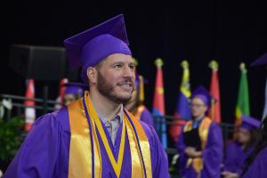 honor student walks proudly across the stage to receive his diploma