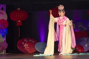 woman dressed in authentic Chinese dress on stage performing a dance