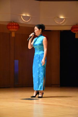 women in blue dress singing on stage