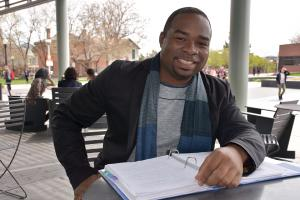 black man at a table smiling