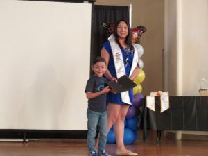woman walking across stage in a blue dress diploma in hand with a little boy in dark shirt and blue jeans