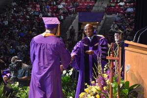 man hands graduate his diploma during commencement