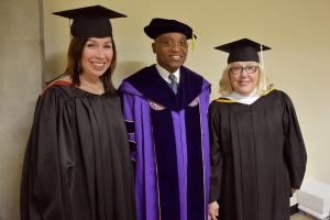 two females and man in black cap and gowns at commencement
