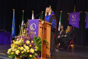 woman standing at podium wearing black and blue cap and gown