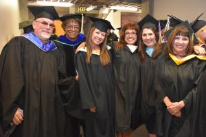 faculty in black cap and gowns smile in a group