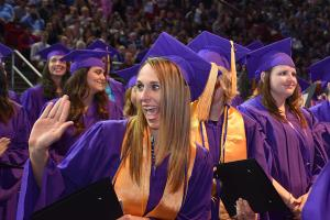 woman in purple cap and gown and gold sash receives a high five in celebration