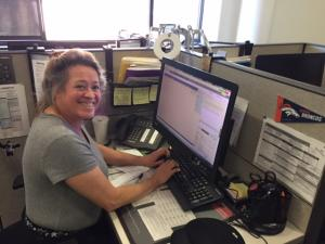 woman in a grey shirt at computer smiling