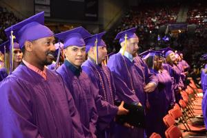 male students wearing purple caps and gowns
