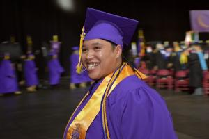 person wearing purple cap and gown and yellow sash indicating honor society