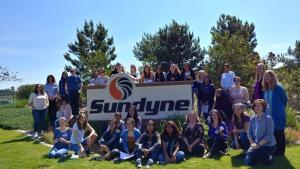 group of people in front of a sign that reads Sundyne