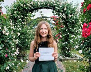young white woman in a green dress holding a certificate in a garden surrounded by flowers