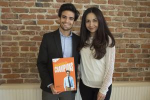 young Hispanic male standing with a Hispanic women smiling and holding a box of cereal