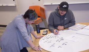 Two people looking at a math problem on a whiteboard.