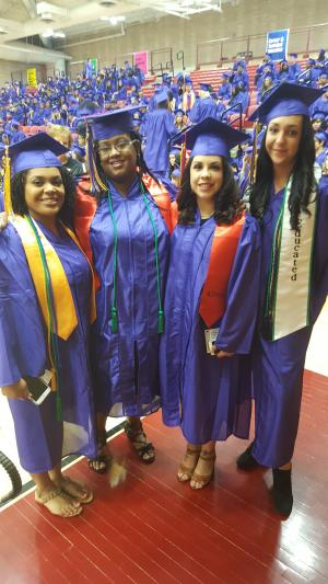 Five young women at graduation in caps and gowns