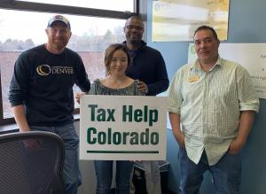 student and her professors standing together, smiling and holding a sign that says Tax Help Colorado