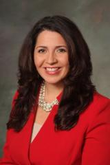 professional headshot of female in red suit jacket