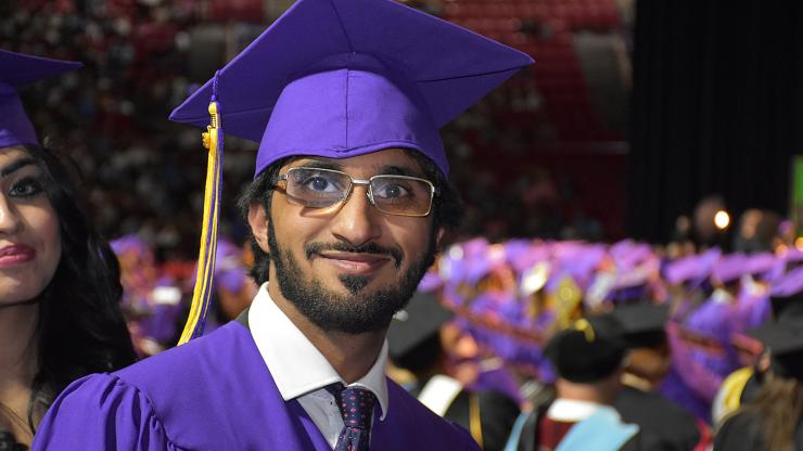 male graduate wearing purple cap and gown smiles proudly
