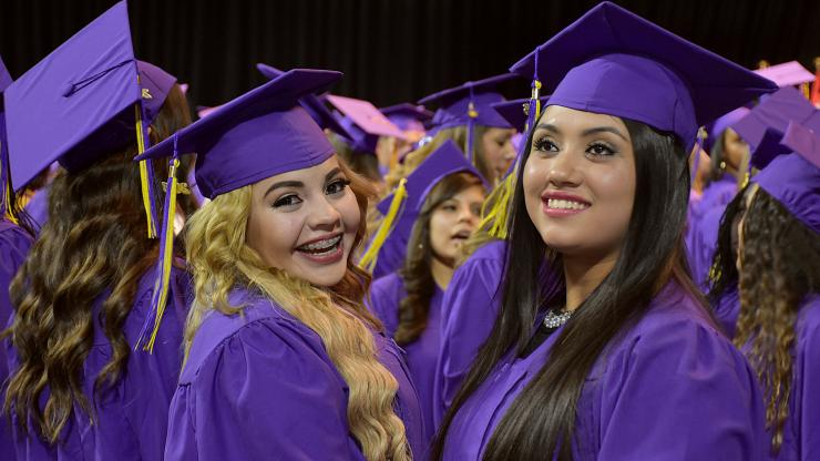 two females wearing cap and gowns at commencement