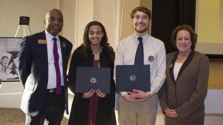 two students holding scholarship awards with the president of the college and system office