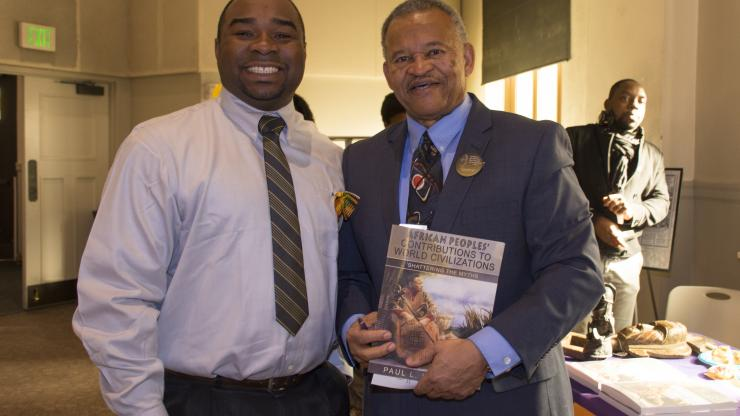 two men, one holding a book he authored