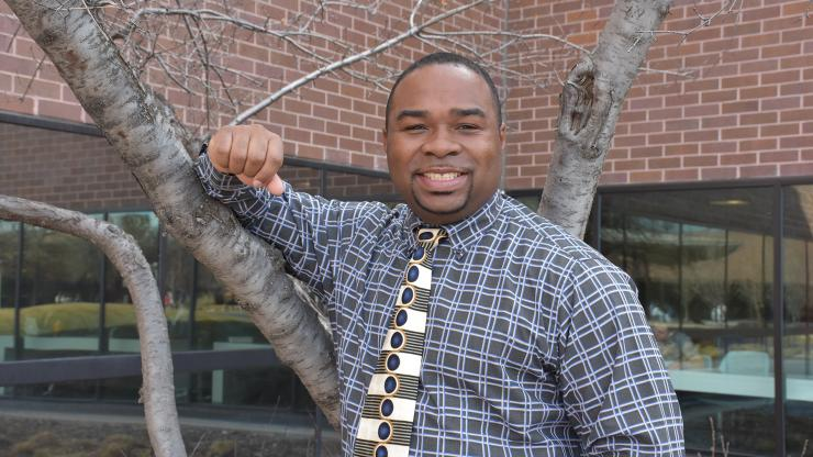 black man standing by a tree smiling