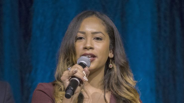 Hispanic woman in a maroon dress speaking into a microphone