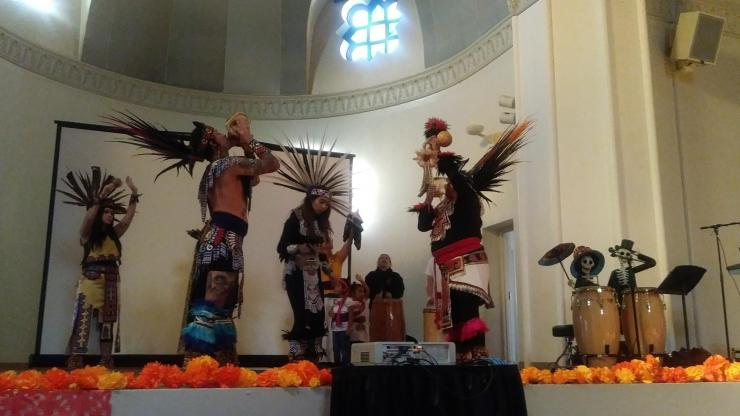 Huitzilopotchli Aztec Dancers in traditional wear, feathers in their hair and bells around their ankles. Drummers in back.