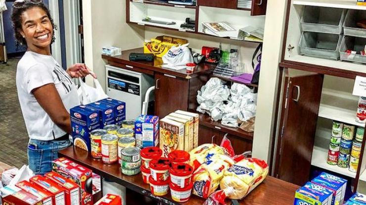 young women standing in front of food pantry food items smiling