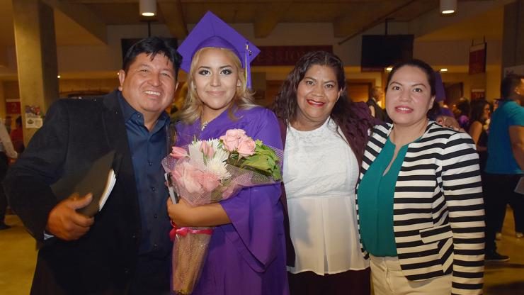woman holding flowers stands with friends and family after graduations