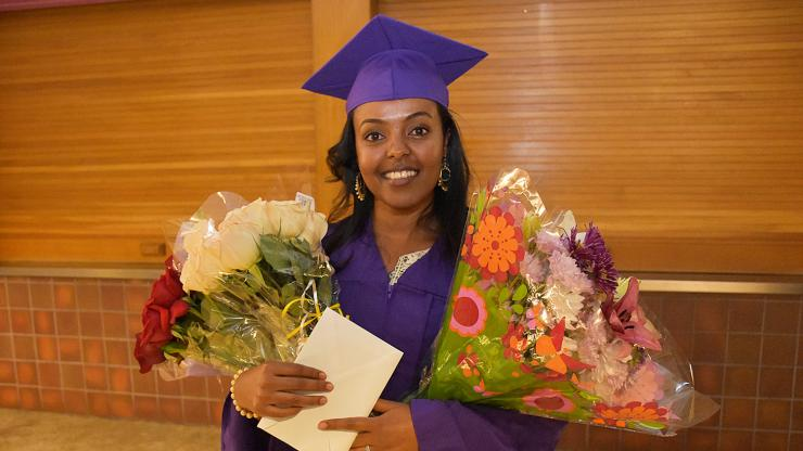smiling woman in purple cap and gown holds celebratory flowers