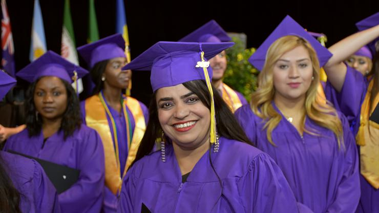 woman with purple cap and gown with other women in the background smiling