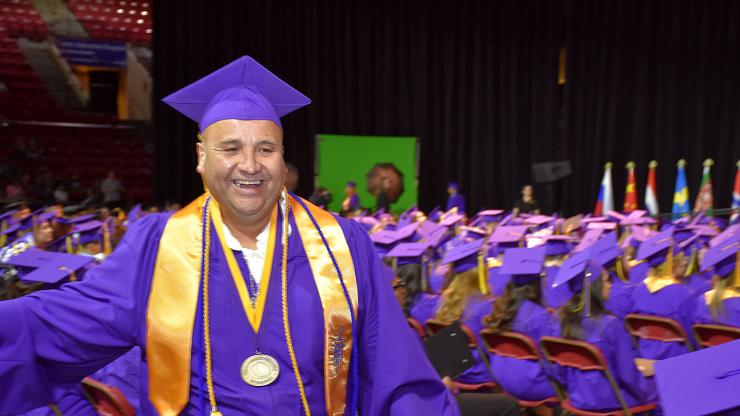 smiling man in purple cap and gown and gold honor society sash receives his diploma
