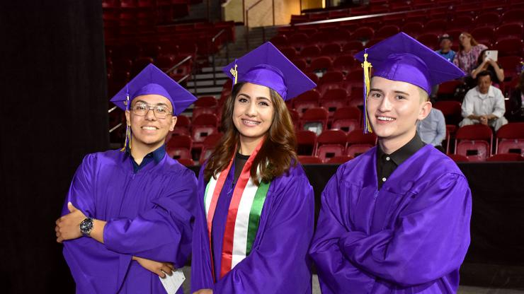 three students in purple cap and gowns standing at graduation