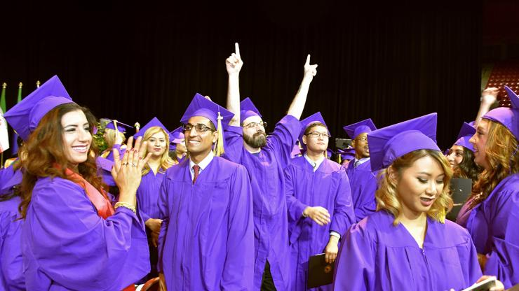 people in purple caps and gowns celebrate with clapping and hands raised in celebration