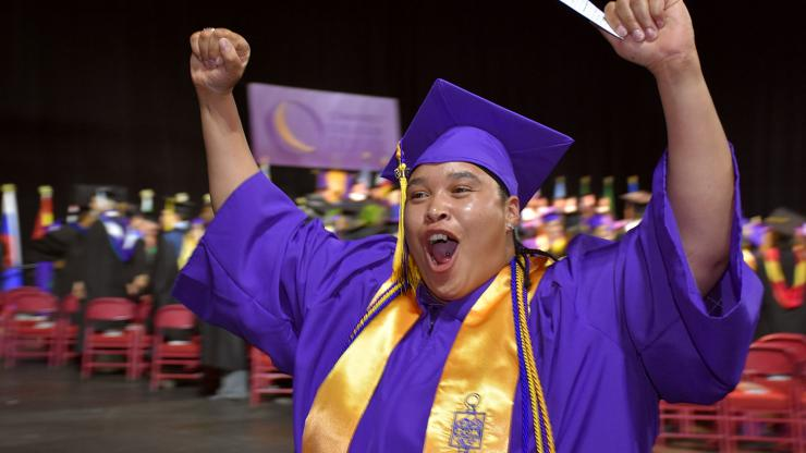 student in purple cap and gown and gold honor society sash holds is hands in the air in celebration