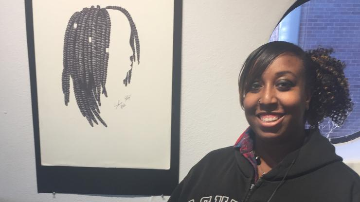 young black woman standing with a drawing smiling