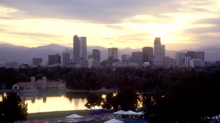 Downtown Denver and mountains from City Park at dusk