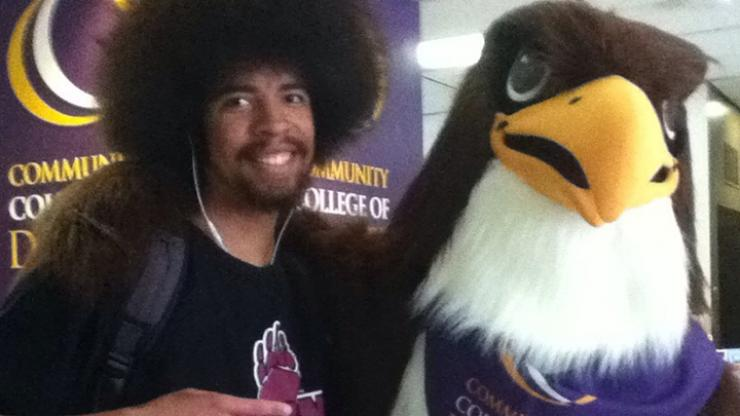 black man standing next to CCD mascot Swoop