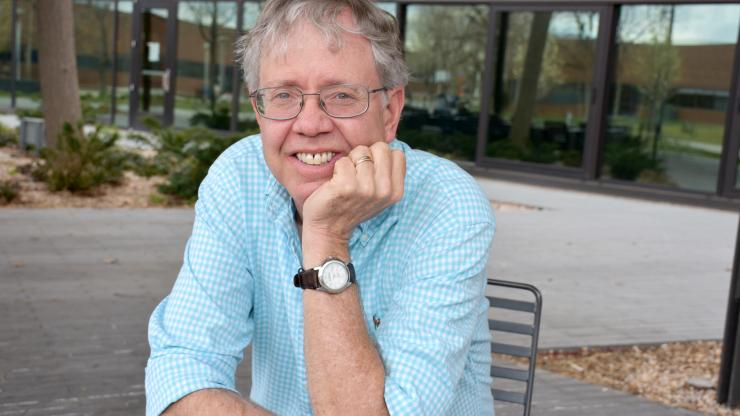 a picutre of a man in a light blue shirt leaning on his hand smiling