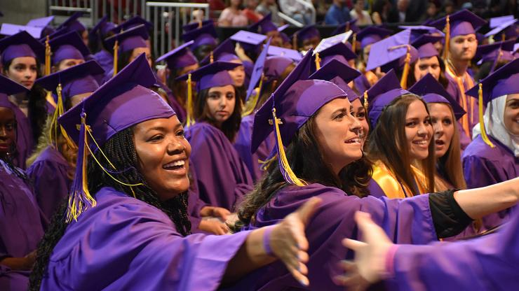 students in purple caps and gowns shake hands in celebration