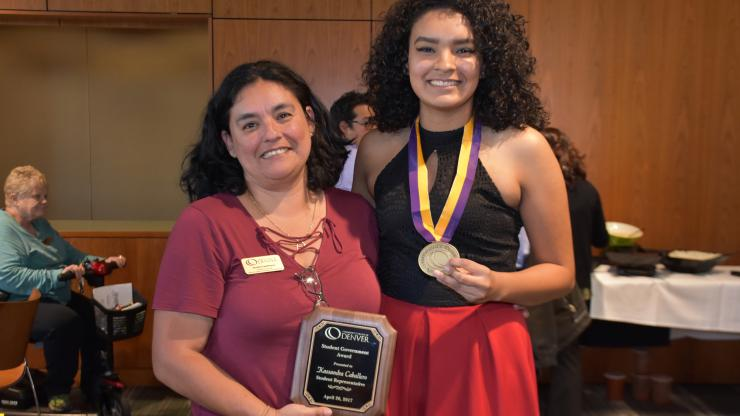 student wearing medal standing next to woman holding award