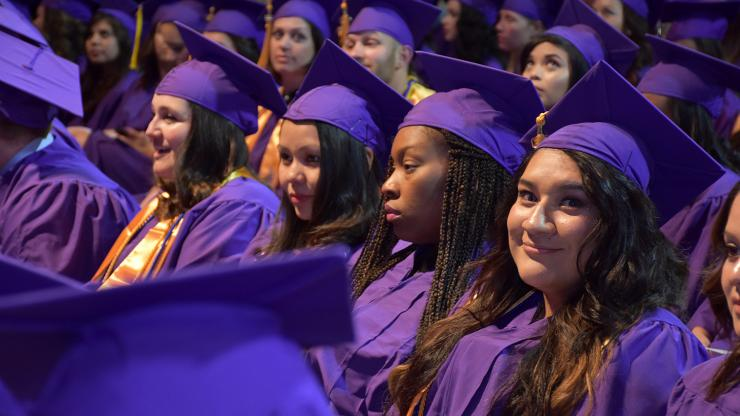 room of people with purple caps and gowns