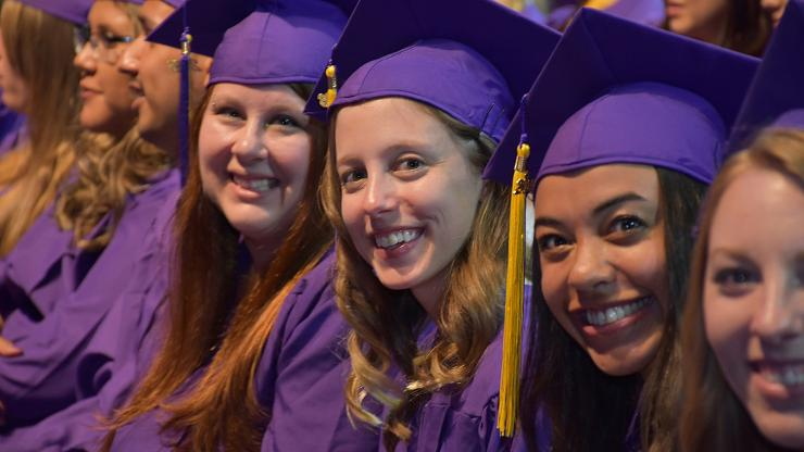 four women sit in a row in purple caps and gowns