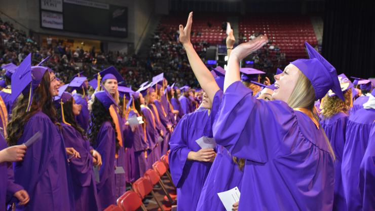people in purple caps and gowns waving