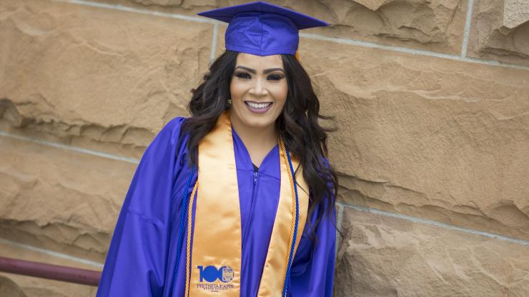 young woman in cap and gown smiling at Commencement